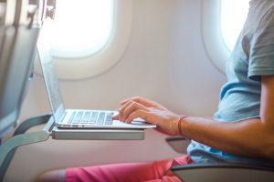 Man Sitting in the Airplane and Working on his Laptop