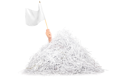 Hand waving white flag from pile of shredded paper isolated on white background