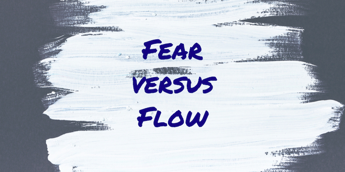 "The words ""Fear Versus Flow"" on white paint"