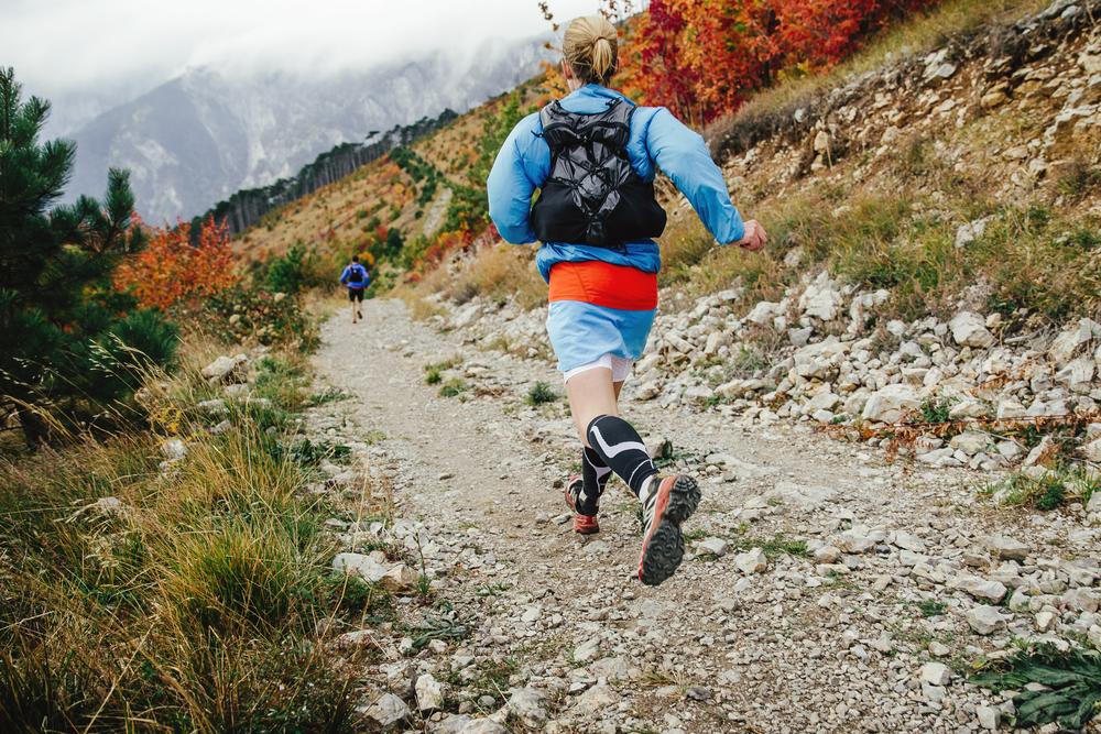 female athlete runner running mountain marathon with backpack
