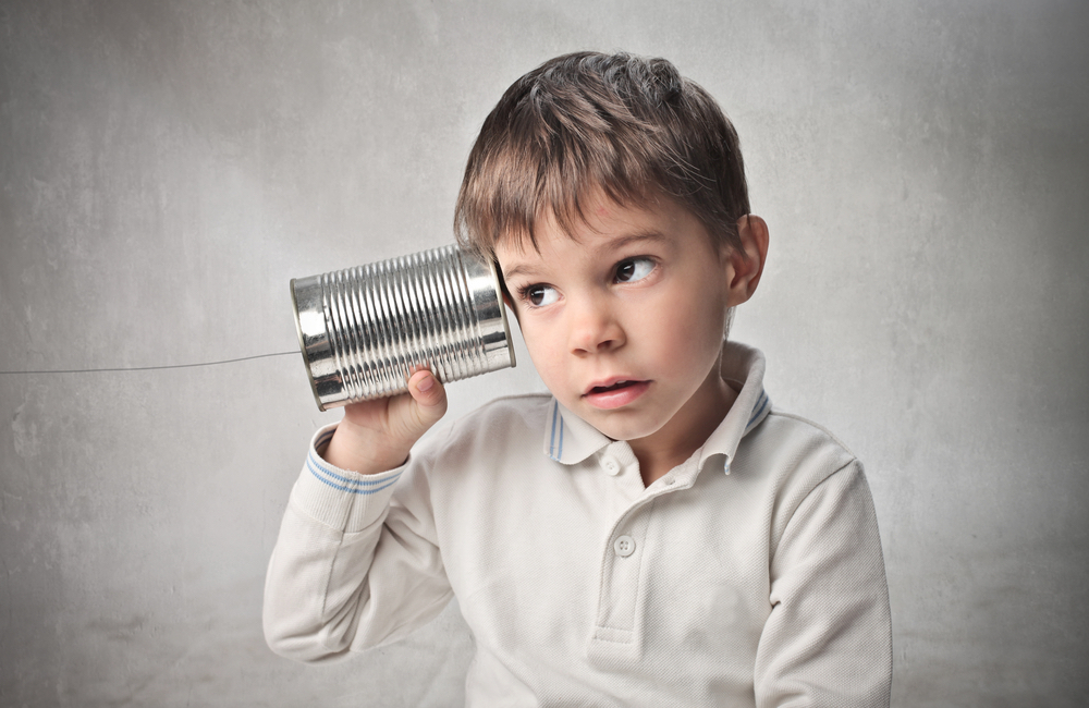 Boy listening to a tin can