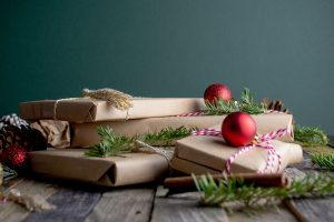 pile of books wrapped in brown paper with greenery