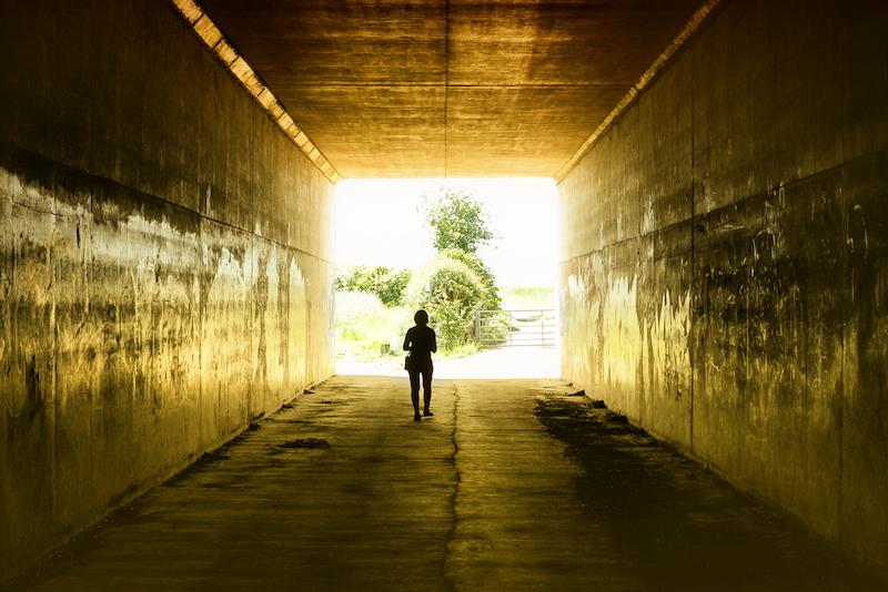 person walking through dark tunnel to sunlight