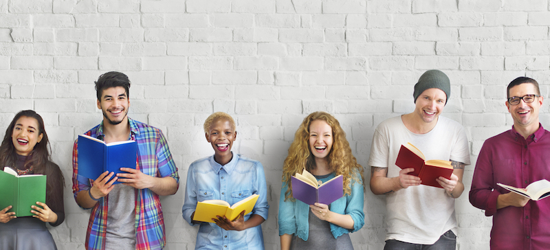 Diverse people holding books and smiling