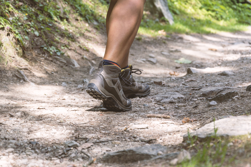Close up of legs with hiking boots on a rugged trail