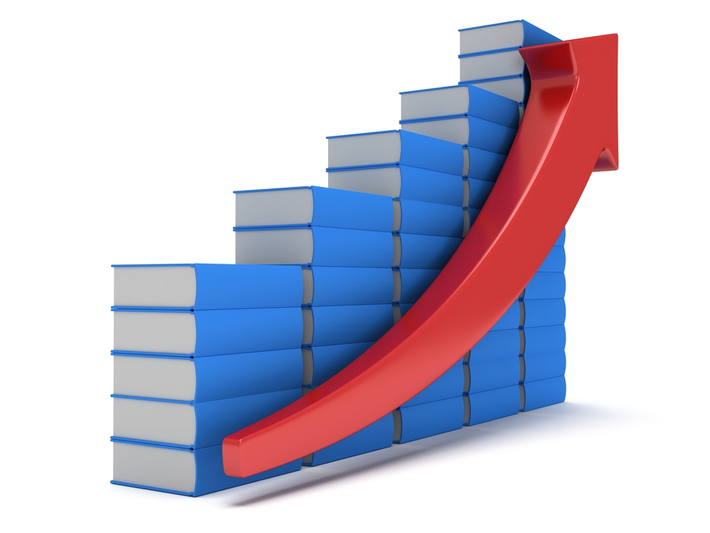 blue books arrayed like a bar chart, with a red arrow indicated growth