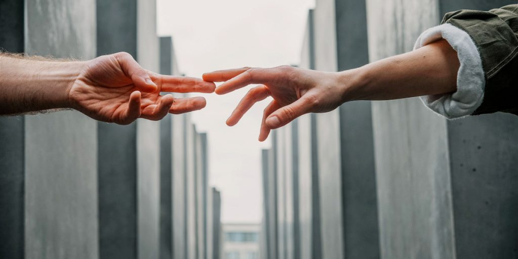 two hands reaching to each other across gray background