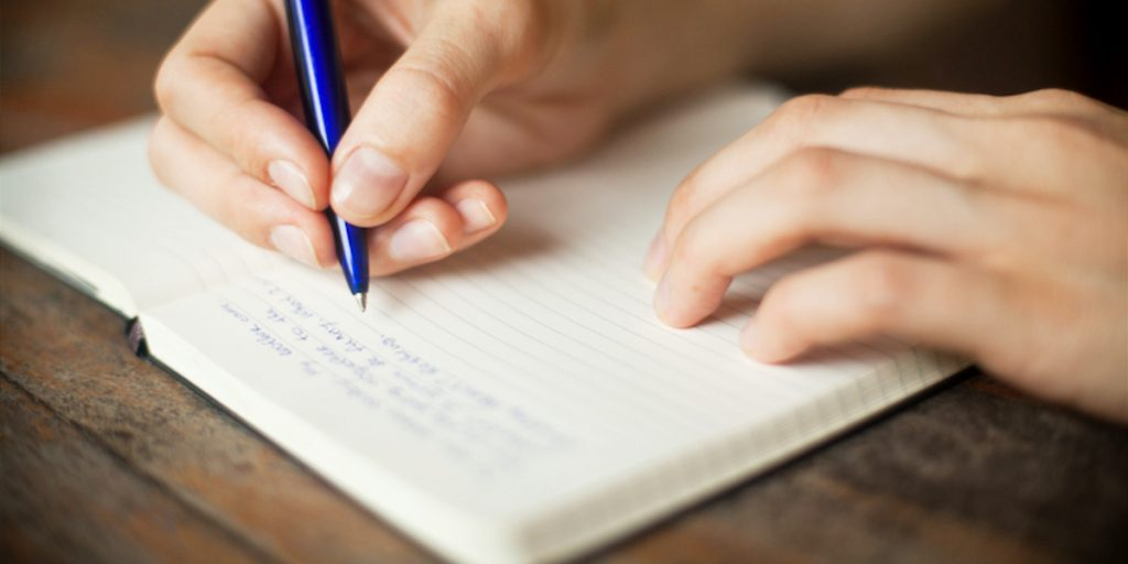 Image of hands writing with a pen in an open journal