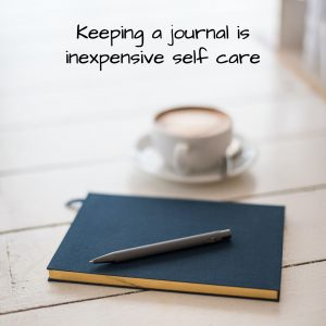 Close journal, pen, and coffee cup on a table.