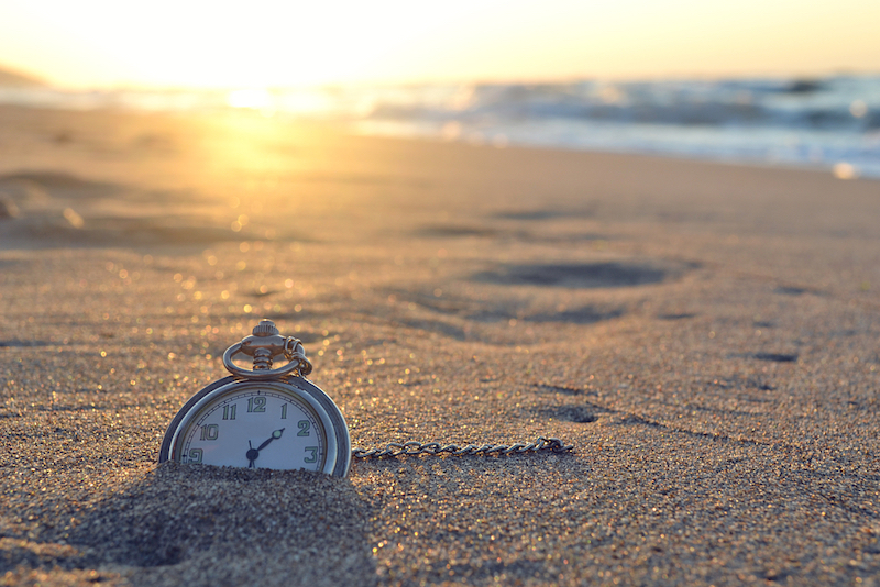 Old-fashioned watch buried in sand at the beach