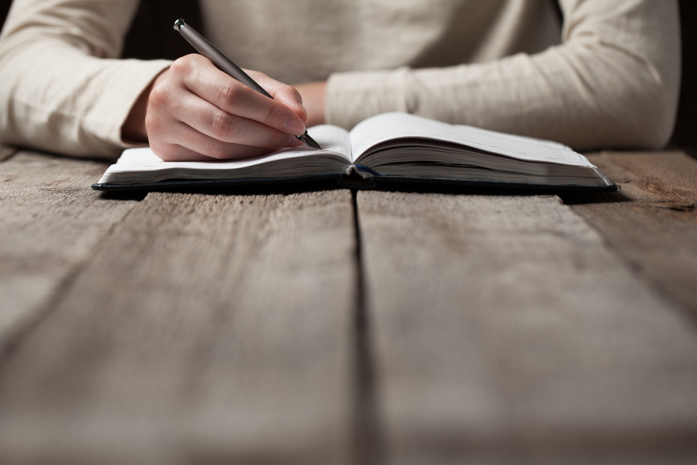 person writing with pen into journal on a wooden table