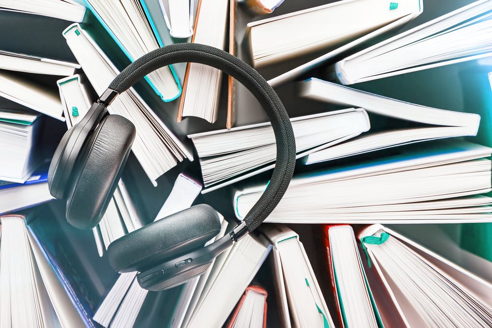 Wireless overhead black headphones lie on a bunch of books.