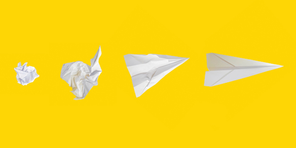 white paper airplanes, from crumpled to smooth, on yellow background